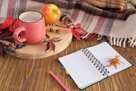 Autumn still life with a cup of cocoa, notebook and apple.