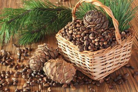 Cedar nuts and cedar cones in a wicker basket on a wooden table