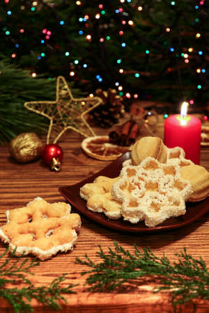 Christmas cookies on a wooden table on a background of glowing Christmas tree garlands