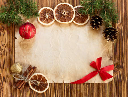 Christmas decorations on the old sheet of paper on a wooden background, place for text