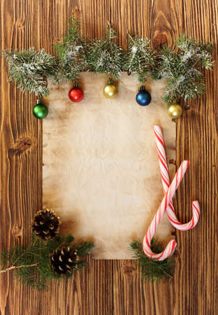 traditional culture: Christmas decorations on the old sheet of paper on a wooden background, place for text