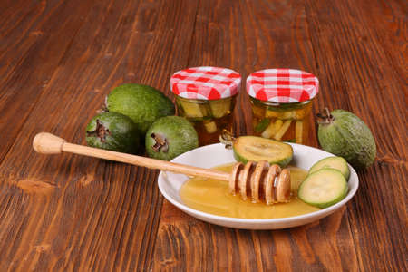 Feijoa Fruits with honey on a wooden table Stock Photo