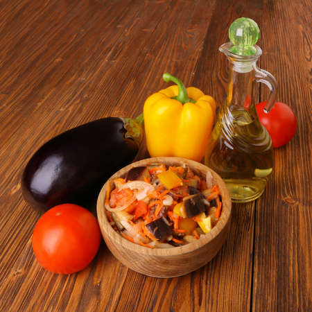 Vegetable salad with eggplant and other ingredients on a wooden table