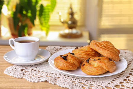 Sweet rolls with raisins and a cup of tea on the table near the window