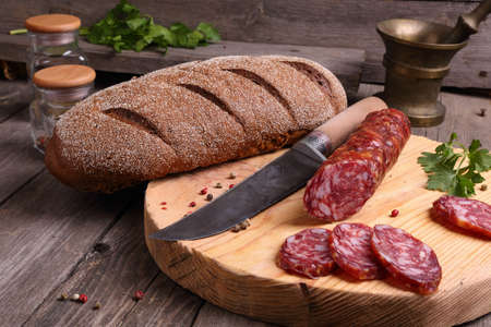 longaniza: Salami, bread and a knife on the kitchen table