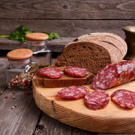 longaniza: Sliced salami and bread on a cutting board, square photo