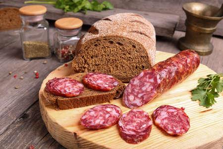 longaniza: Sliced salami and bread on a cutting board