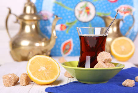 Turkish tea with cane sugar and lemon on a white table Stock Photo