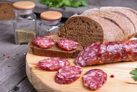 longaniza: Sliced salami and bread on the kitchen table Stock Photo