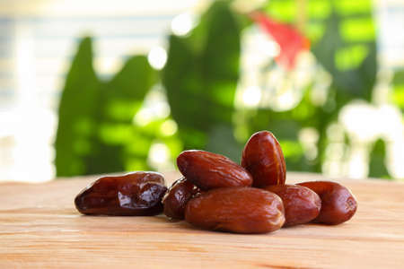 A handful of dates on the wooden table against the window