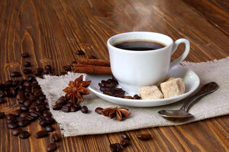 Cup of coffee with cane sugar and cinnamon on the table