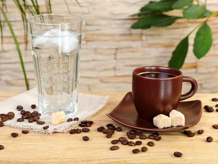 Cup of black coffee and a glass of cold water on a wooden table