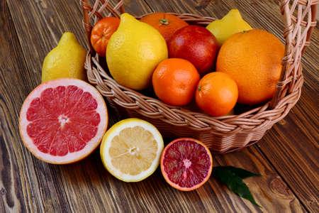 Citrus fruits - oranges, lemons, tangerines, grapefruit on a wooden table Stock Photo