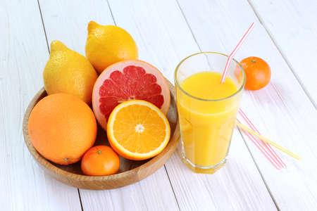 orange peel clove: Citrus fruits - oranges, lemons, tangerines, grapefruit and a glass of orange juice on a wooden table