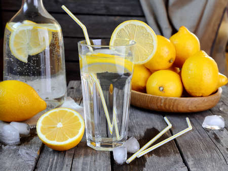 Lemonade in a transparent glass and lemons on a gray wooden table