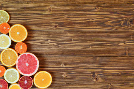 citricos: Citrus fruta cortada por la mitad - naranjas, limones, mandarinas, pomelo en un fondo de madera