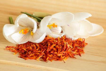 Saffron spice and flower crocus  on a wooden background
