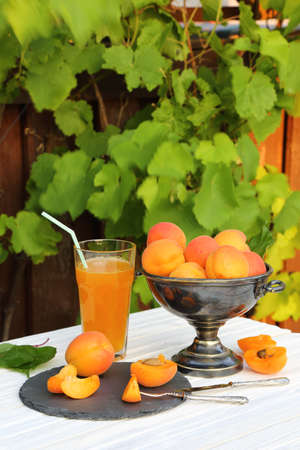 Apricots in a metal vase and a glass of apricot juice on white wooden table in the garden Stock Photo