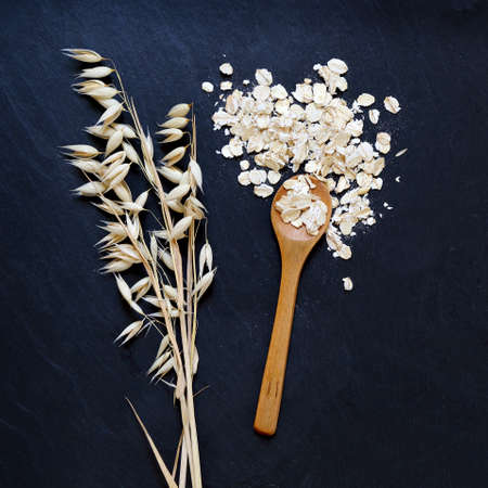 petit dejeuner: flocons d'avoine et les oreilles d'avoine de grains sur fond noir
