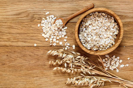 Rolled oats and oat ears of grain on a wooden table, copy space