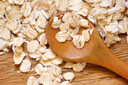 Rolled oats and oat ears of grain on a wooden table, close-up