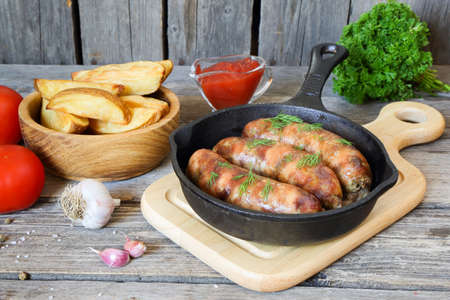 Grilled meat sausages and potatoes in a pan on the table