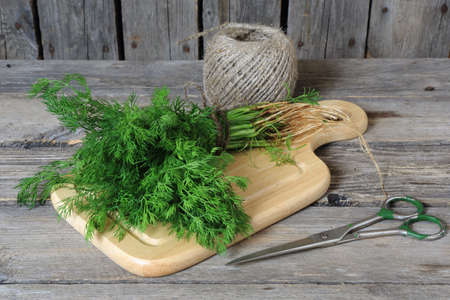 Bunch of dill on a cutting board on a gray wooden table