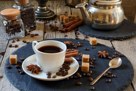 Black coffee with cinnamon, anise and cane sugar on a wooden table