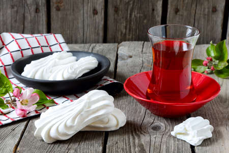 kiss biscuits: Meringues and cup of tea on a gray wooden table Stock Photo