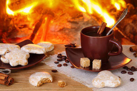 Cup of coffee with spices and gingerbread  in the background of a burning fireplace Stock Photo