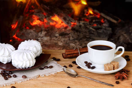 Cup of coffee with spices and marshmallows on a background of a burning fireplace