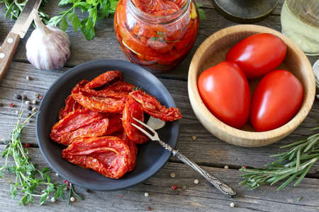 Sun dried tomatoes and ingredients to prepare them on a wooden table