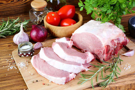 Raw pork fillet on a cutting board, cut into steaks Stock Photo