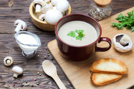 Mushroom soup puree of champignon in a brown cup on a wooden table Stock Photo