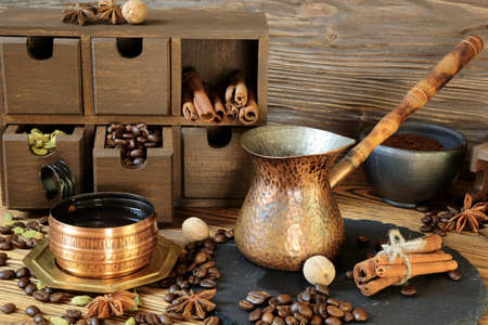 Black coffee in a copper cup and spices on a wooden table