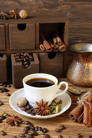 Black coffee in a white cup and spices on a wooden table Stock Photo