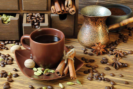 Black coffee in brown cup and spices on a wooden table