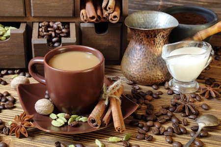 Coffee with milk and spices on a wooden table Stock Photo