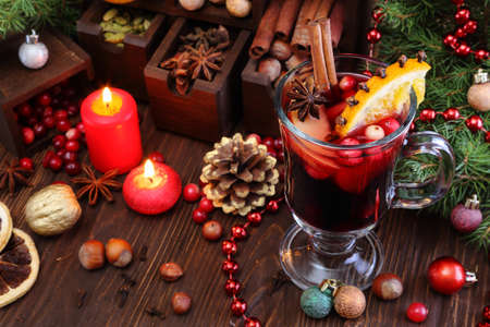 Christmas mulled wine with apple, cranberry, orange and spices on a wooden table Stock Photo