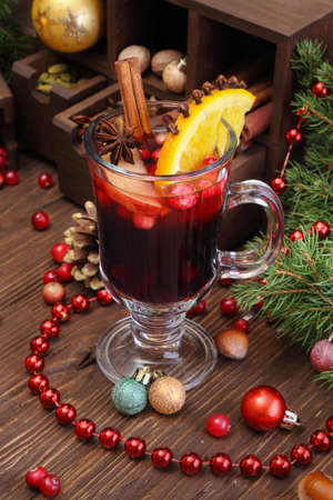Christmas mulled wine with apple, cranberry, orange, spices and chocolate on a wooden table Stock Photo