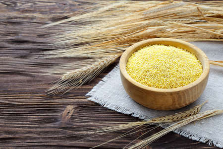 Millet in a bowl and wheat ears on a brown wooden table