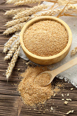 Bran in a bowl and wheat ears on a brown wooden table Stock Photo