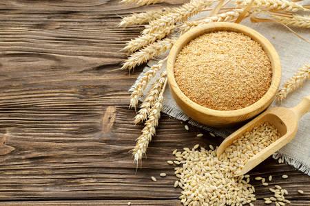 茶色の木製のテーブルに米ぬか、穀物、小麦の耳