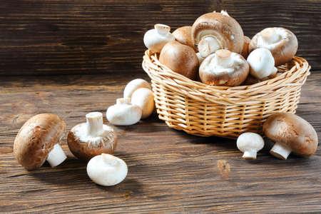 Portobello champignons in a wicker basket on a brown table Stock Photo