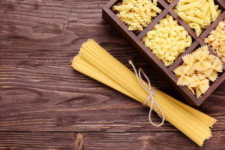 Italian pasta in assortment, several different varieties separated in a decorative box,  on a brown wooden background, place for text