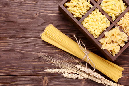 Italian pasta in assortment several different varieties separated in a decorative box, spaghetti and ears on a brown wooden background Stock Photo