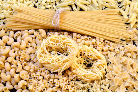 Spaghetti, noodles, pasta of different kinds, scattered on the table, top view