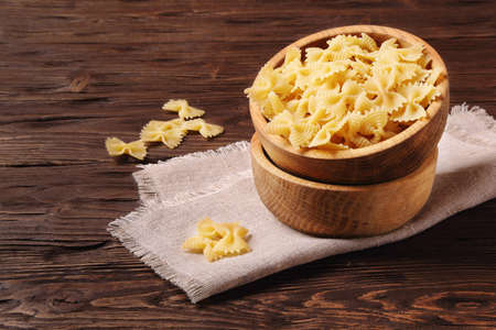Pasta farfalle in a wooden bowl on the table