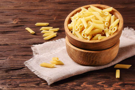 Raw pasta penne in a wooden bowl on the table