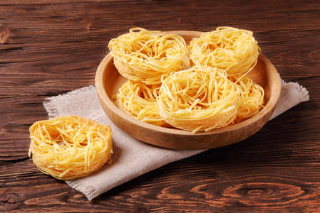 Raw pasta fettuccine in a wooden bowl on the table Stock Photo